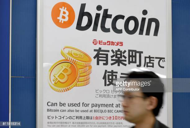 This picture taken on April 7 2017 shows a man walking past a signboard informing customers that Bitcoin can be used for payment at a store in Tokyo...