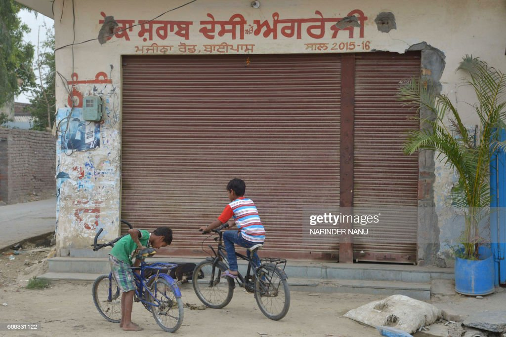 This picture taken on April 7 2017 shows children cycling in front of a closed liquor shop near a national highway on the outskirts in Amritsar...