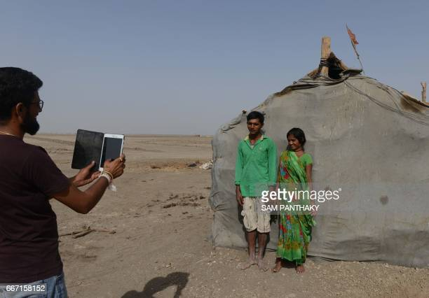 This picture taken on April 7 2017 shows Dhvanit Pandya program coordinator of Agariya Heetrakshak Manch taking pictures using a tablet computer of...