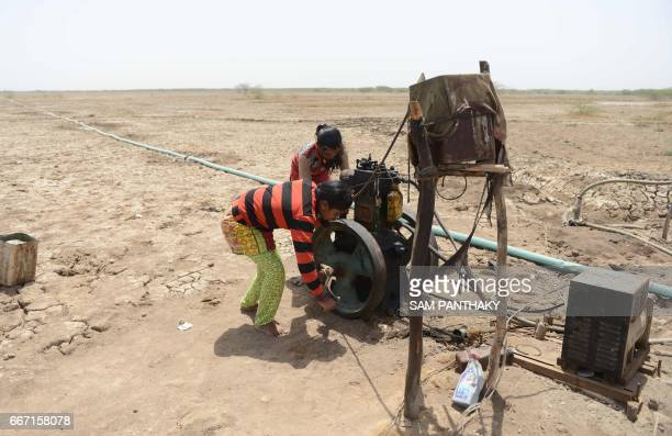 This picture taken on April 7 2017 shows Indian salt pan worker Puja Ganeshbhai Muladiya and with her sister Aaarti trying to start a diesel pump...