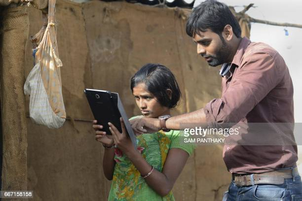 This picture taken on April 7 2017 shows Rahul Chaudhry project coordinator from Digital Empowerment Foundation showing a tablet computer to salt pan...