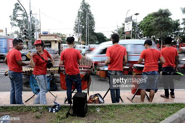 This picture taken on April 8 2016 shows a group of Indonesian buskers performing with the traditional angklung music at a street junction in Jakarta...