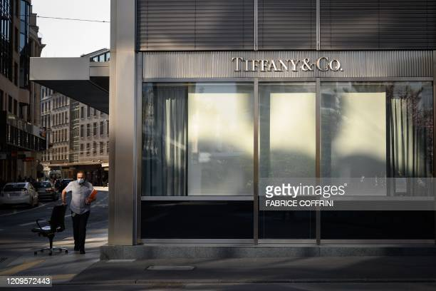 This picture taken on April 8, 2020 in Geneva shows a man wearing a protective mask pulling a chair next to a closed store of US luxury jewelry...