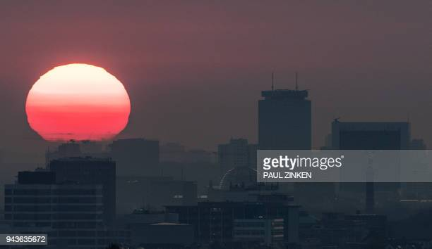 TOPSHOT This picture taken on April 9 2018 shows the sun rising over the tower of the city in Berlin / AFP PHOTO / dpa / Paul Zinken / Germany OUT