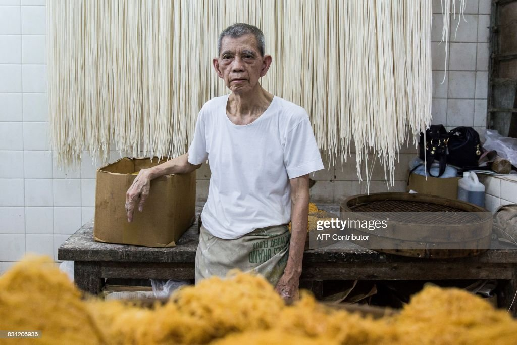 This picture taken on August 1, 2017 shows Ho Shun-kan posing for a photo in his shop, Kan Kee Noodles, where he makes different types of noodles that he sells direct to customers and surrounding restaurants, in the Central district of Hong Kong. From decades-old holes in the wall to multi-million dollar businesses, Hong Kong's noodle scene is a sprawling moneyspinner in a city that runs on quick and affordable comfort food. / AFP PHOTO / Isaac LAWRENCE / TO GO WITH HongKong-lifestyle-food-noodles-business, FEATURE by Elaine YU