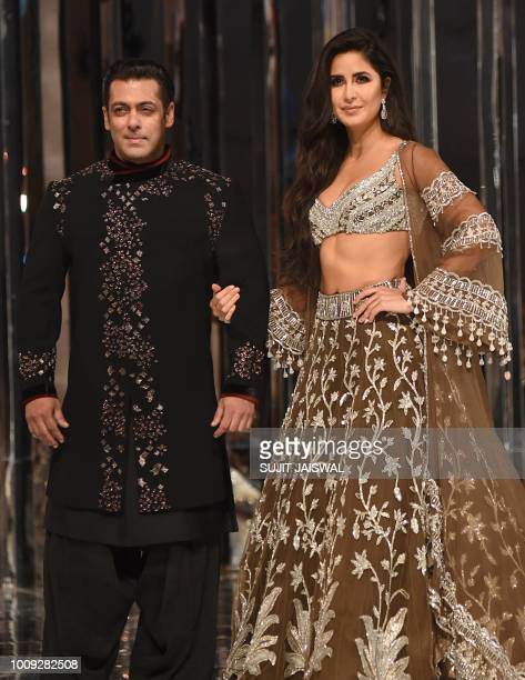 This picture taken on August 1 2018 shows Bollywood actors Salman Khan and Katrina Kaif presenting creations by designer Manish Malhotra during a...