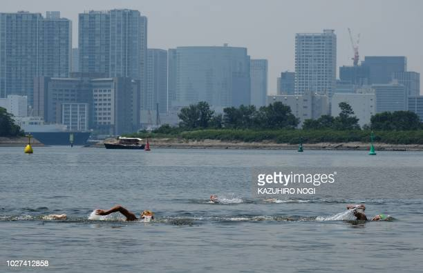 This picture taken on August 1 2018 shows swimmers in the water at the Odaiba seaside park in Tokyo Bay On a blazing hot Tokyo summer day children...