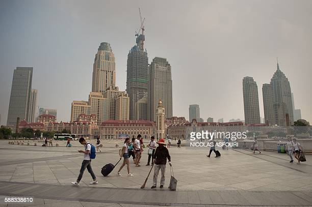 This picture taken on August 10 2016 shows people walking in front of the main train station in Tianjin the city where one year ago a fire and huge...