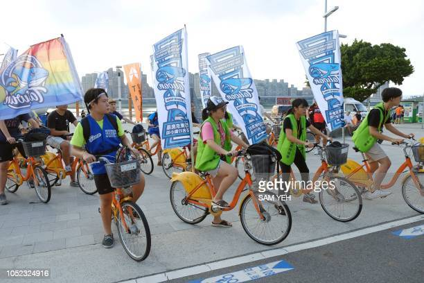 This picture taken on August 10 2018 shows proTaiwan independence activists riding bicycles with flags to promote a referendum on the streets in...