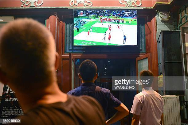 This picture taken on August 11 2016 shows a group of men watching a TV broadcast of the basketball match between China and Venezuela at the Rio 2016...