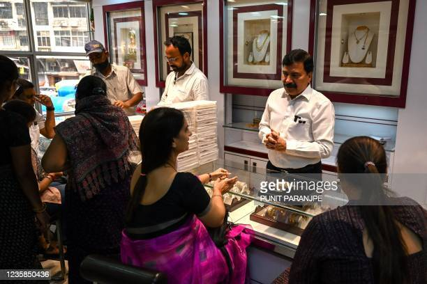 This picture taken on August 11, 2021 shows a shop manager speaking with customers at a jewellery shop in Mumbai. - Desperate for cash, many families...
