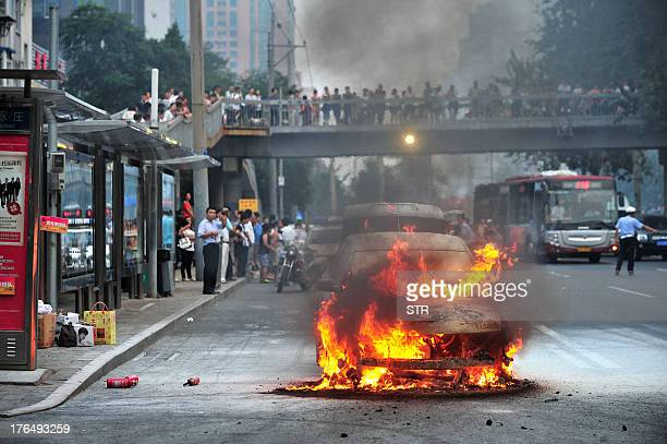This picture taken on August 13 2013 shows a car burning on a road in downtown Beijing The only passenger in the car the driver managed to get out...