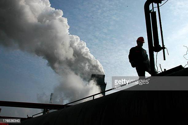 This picture taken on August 14, 2013 shows laborers working in a coal chemical factory in Huaibei, east China's Anhui province. China has soared...