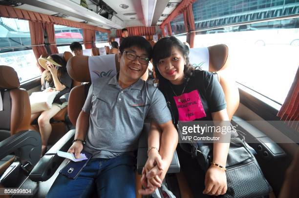 This picture taken on August 14 2017 shows Vietnamese bride Huynh Thi Thai Muoi and her South Korean husband Kim KyeongBok in a bus going to Kim's...