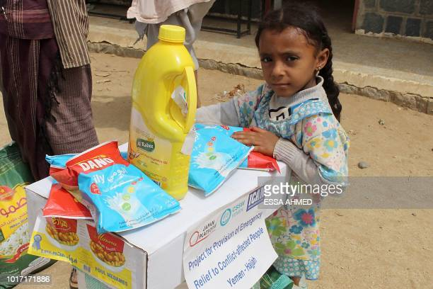 This picture taken on August 15, 2018 shows a displaced Yemeni child from Hodeida receiving food aid from a Japanese NGO in the northern district of...