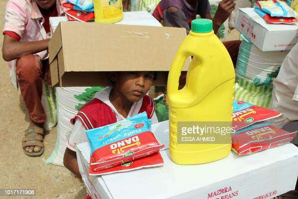 This picture taken on August 15 2018 shows a displaced Yemeni child from Hodeida receiving food aid from a Japanese NGO in the northern district of...