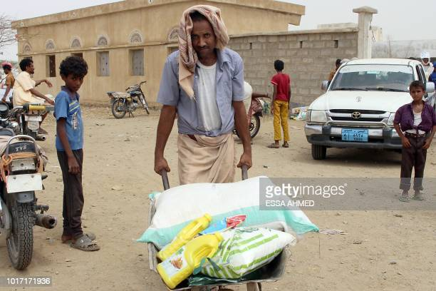This picture taken on August 15 2018 shows a displaced Yemeni man from Hodeida carrying food aid from a Japanese NGO in a barrow in the northern...