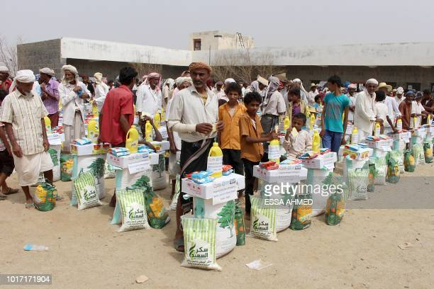 This picture taken on August 15 2018 shows displaced Yemenis from Hodeida receiving food aid from a Japanese NGO in the northern district of Abs in...