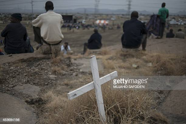 This picture taken on August 16 2014 shows a white cross as people gather in Marikana next to the hill where two years ago miners where gunned down...