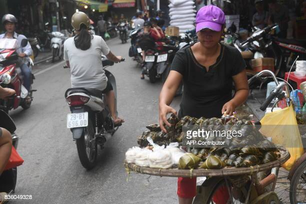 This picture taken on August 17 2017 shows a mobile vendor selling foods on a street in downtown Hanoi / AFP PHOTO / HOANG DINH NAM