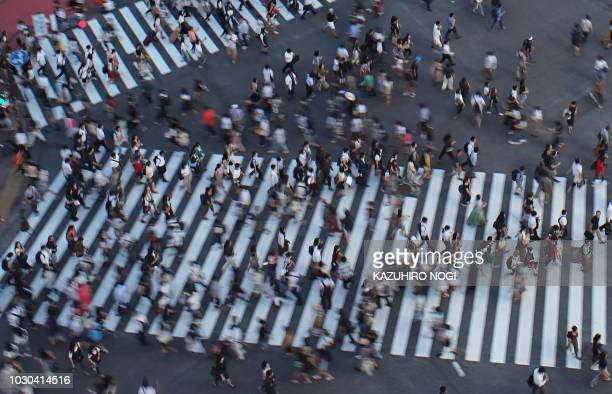 TOPSHOT This picture taken on August 17 2018 shows people crossing a scramble intersection in Tokyo's shopping district Shibuya Japan's economy grew...