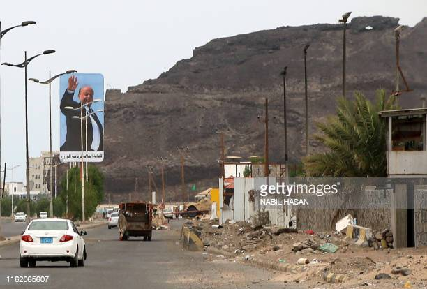 This picture taken on August 17, 2019 shows cars driving beneath a large billboard showing Yemen's internationally recognised government of President...