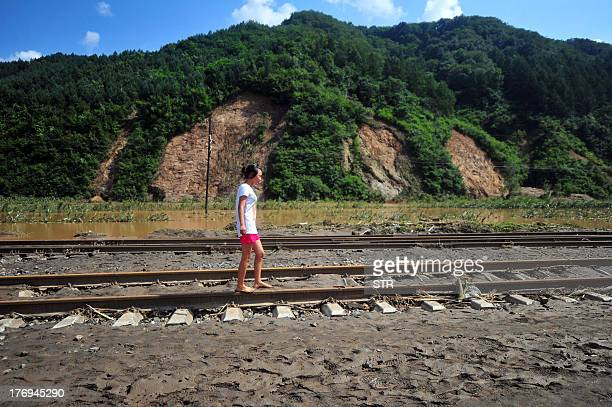 This picture taken on August 18 2013 shows a girl walking barefoot on train track covered with mud after floods hit the Qingyuan Manchu autonomous...