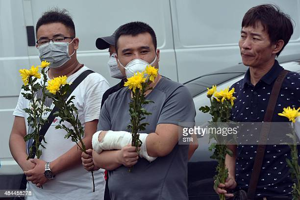 This picture taken on August 18 2015 shows an injured man holding flowers during a vigil for firefighters and soldiers killed during the explosions...
