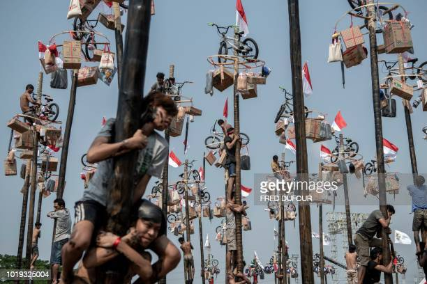 TOPSHOT This picture taken on August 18 2018 shows participants taking part in Panjat Pinang a pole climbing contest as part of the 2018 Asian Games...