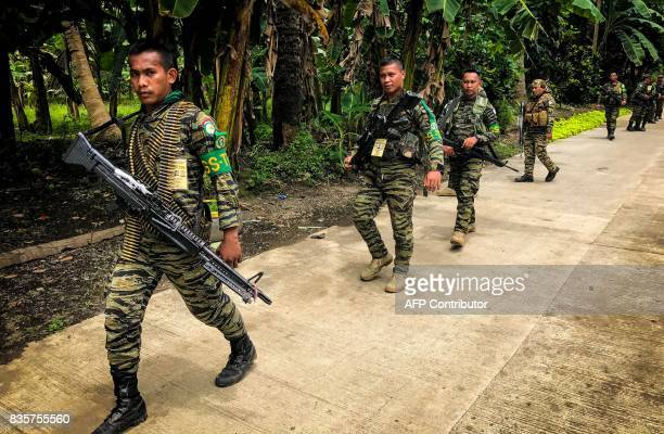 This picture taken on August 19 shows members of Moro Islamic Liberation Front patroling a road in Maguindanao on the southern Philippine island of...