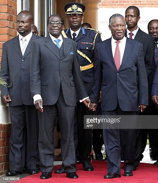 This picture taken on August 2 2012 shows Zimbabwean President Robert Mugabe flanked by Zambian President Michael Sata posing at the State House in...