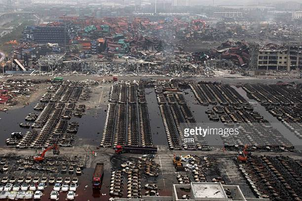 This picture taken on August 20, 2015 shows excavators cleaning up damaged cars during the explosions in Tianjin. Cyanide levels more than 350 times...