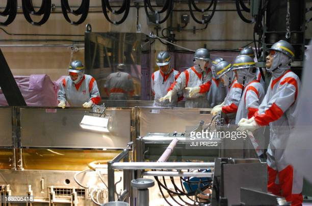 This picture taken on August 21 2010 shows members of the Fukushima prefectural assembly observing an operation of the MOX fuel storage pool inside...