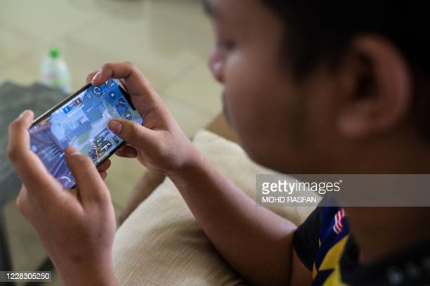 This picture taken on August 22, 2020 shows stateless eSports player Muhammad Aiman Hafizi Ahmad playing PlayerUnknown's Battlegrounds , an online...