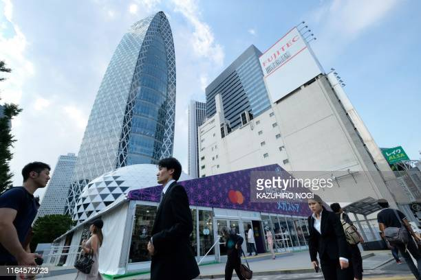 This picture taken on August 26 2019 shows pedestrians walking past the Rugby World Cup 2019 megastore in Tokyo's bustling Shinjuku district With...