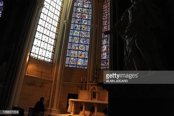 This picture taken on August 26 shows a visitor in one of three restored chapels in the 13th century Cathedral of Chartres western France Considered...