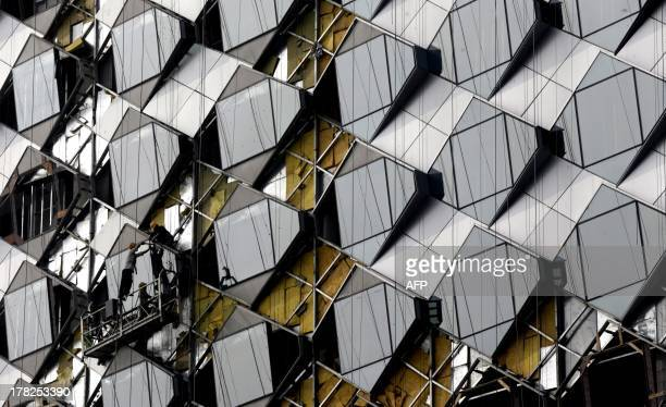 This picture taken on August 27 2013 shows laborers working on the wall of the Wanda Reign Wuhan Hotel which is under construction in Wuhan central...