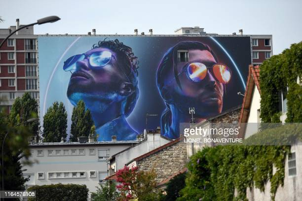 This picture taken on August 28, 2019 shows a giant banner depicting the two brothers Ademos and N.O.S of the French rap group PNL , set up on a...