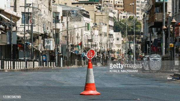 This picture taken on August 28, 2020 shows a view of traffic cone topped with a small stop sign in the middle of an empty road during a COVID-19...