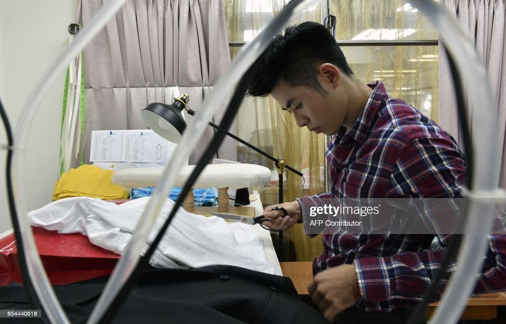 This picture taken on August 29, 2017 shows Taiwanese 'qipao' maker Lee Wei-fan working at his studio in Taipei. Lee studied qipao making under an old master for five years after deciding to carve out a niche in a field few of his design peers wanted to go into. / AFP PHOTO / SAM YEH / TO GO WITH Taiwan-China-fashion-culture-qipao,FEATURE by Amber WANG