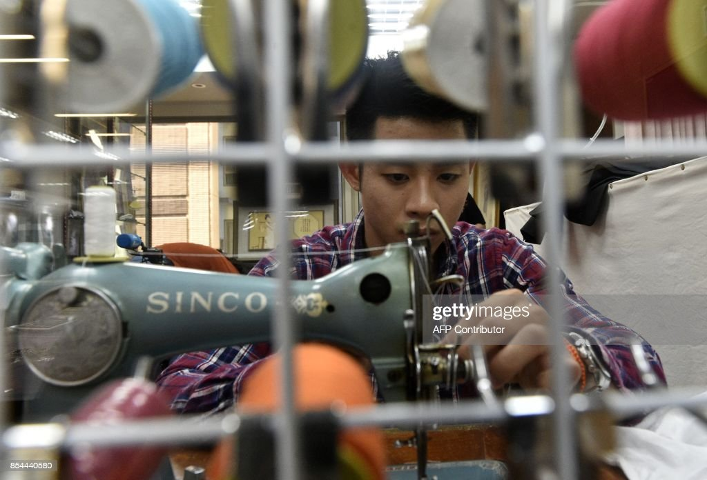 This picture taken on August 29, 2017 shows Taiwanese 'qipao' maker Lee Wei-fan sewing at his studio in Taipei. Lee studied qipao making under an old master for five years after deciding to carve out a niche in a field few of his design peers wanted to go into. / AFP PHOTO / SAM YEH / TO GO WITH Taiwan-China-fashion-culture-qipao,FEATURE by Amber WANG