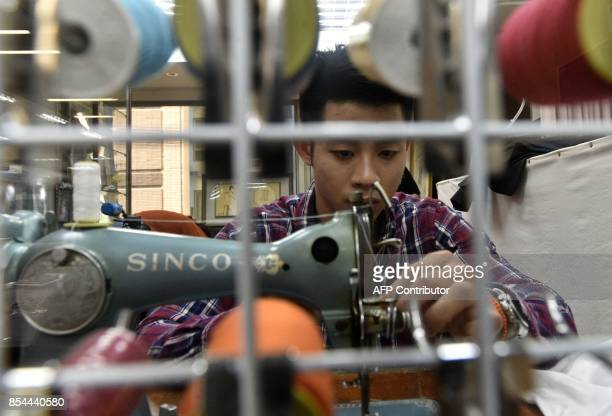 This picture taken on August 29 2017 shows Taiwanese 'qipao' maker Lee Weifan sewing at his studio in Taipei Lee studied qipao making under an old...