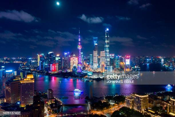 TOPSHOT This picture taken on August 29 2018 shows the moon shining over the financial district of Pudong in Shanghai