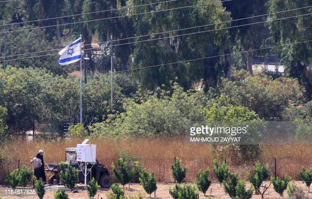 This picture taken on August 29 2019 from the Lebanese village of Kfar Kila in southern Lebanon along the border with Israel shows Israeli farmers...