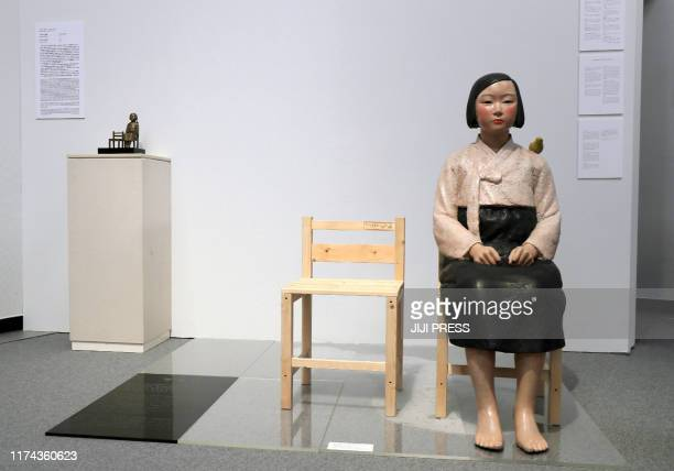 This picture taken on August 3, 2019 shows a statue of a girl in traditional Korean clothes sitting on a chair, one of art works in the exhibition of...