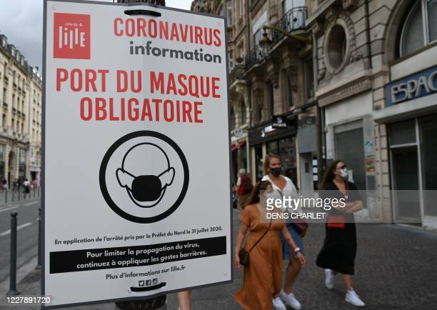 """This picture taken on August 3, 2020 shows a sign reading """" Wearing protective mask is mandatory """" on a street in Lille, northern France, as city of..."""