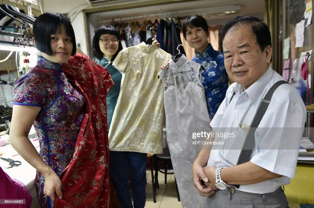 This picture taken on August 30, 2017 shows Taiwanese 'qipao' maker Lin Chin-te (R) and his students posing for photos at his studio in Taipei. Lin Chin-te, 74, is among a handful of craftsmen in Taiwan who still specialise in handmaking the high-collar, figure-hugging garment which was once part of many women's daily wardrobes. / AFP PHOTO / SAM YEH / TO GO WITH Taiwan-China-fashion-culture-qipao,FEATURE by Amber WANG