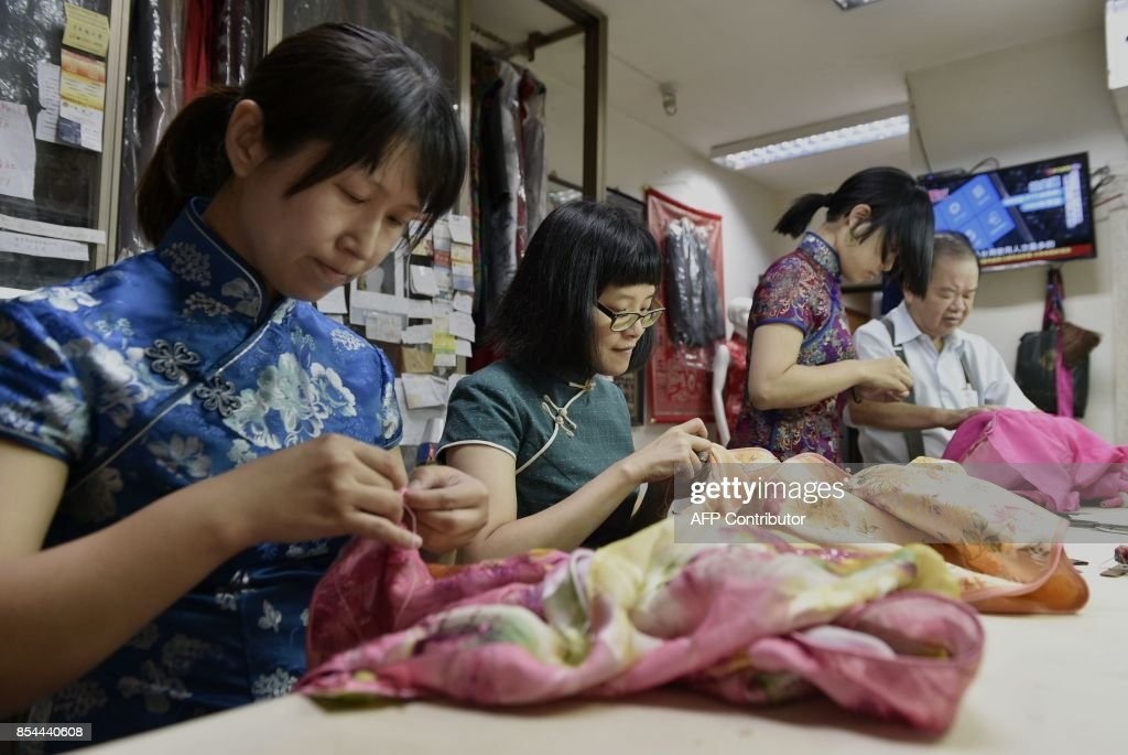 This picture taken on August 30, 2017 shows Taiwanese 'qipao' maker Lin Chin-te (far R) working with students at his studio in Taipei. Lin Chin-te, 74, is among a handful of craftsmen in Taiwan who still specialise in handmaking the high-collar, figure-hugging garment which was once part of many women's daily wardrobes. / AFP PHOTO / SAM YEH / TO GO WITH Taiwan-China-fashion-culture-qipao,FEATURE by Amber WANG