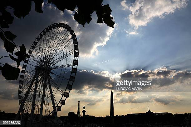 This picture taken on August 30 shows the sun setting down over the Eiffel Tower the Place de la Concorde obelisk the Grand Palais and the big wheel...