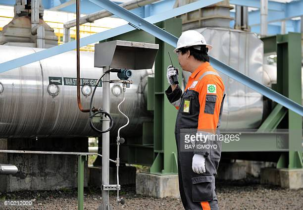 This picture taken on August 31 2016 shows a plant technician using a walkietalkie as he inspects machinery at the Wayang Windu geothermal power...